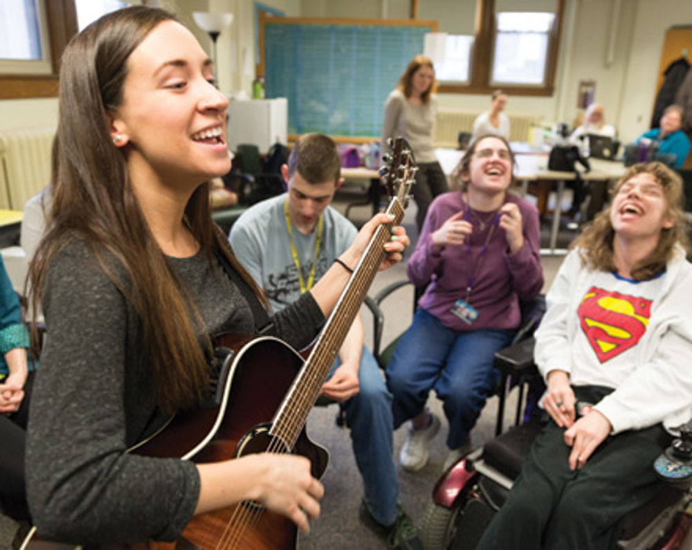 Students signing and playing guitar and being happy
